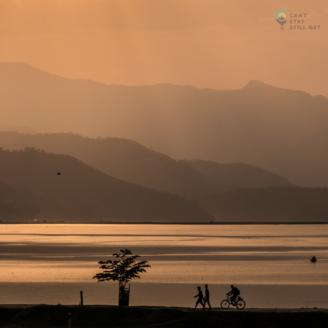 biker and two pedestrians by the lake in Pokhara in the sunset orange light