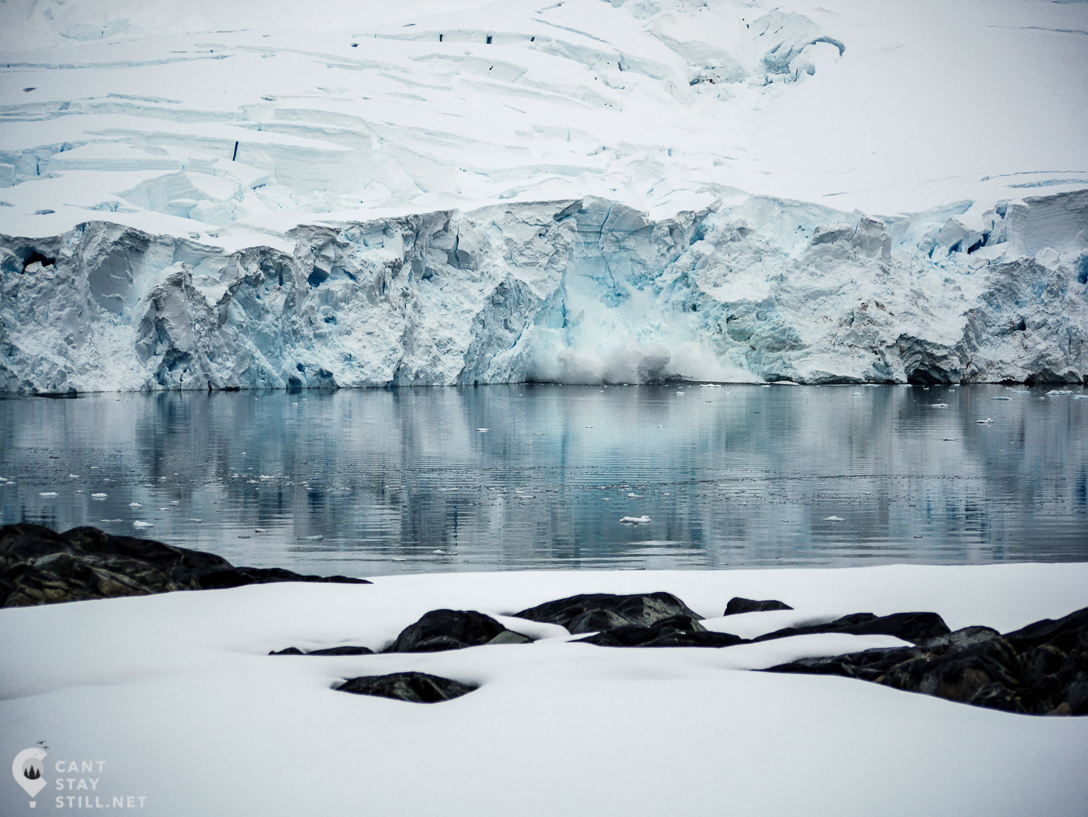 the silence and the perfect mirror of the water are broken by the ice calving from a glacier in Antarctica