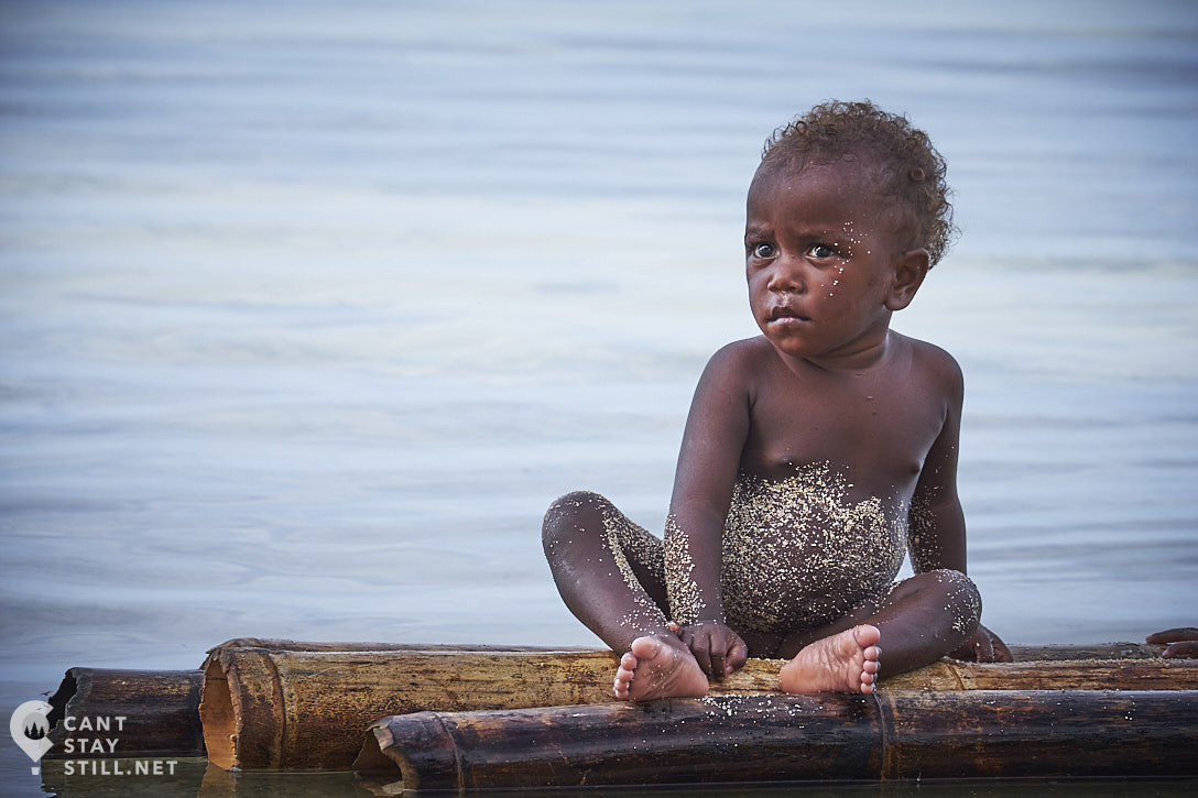 a toddler covered in sand on a raft in New Ireland, Papua New Guinea
