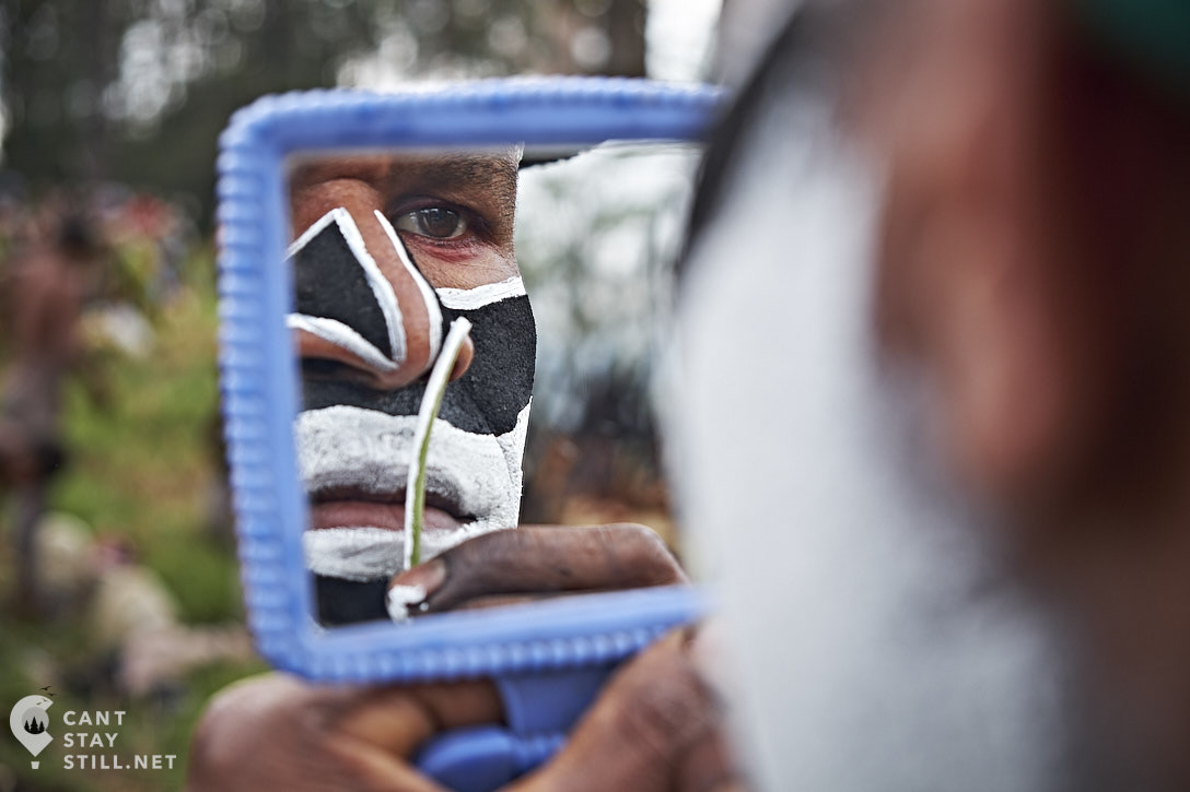man applying facepaint at the Mt. Hagen Show in Papua New Guinea PNG